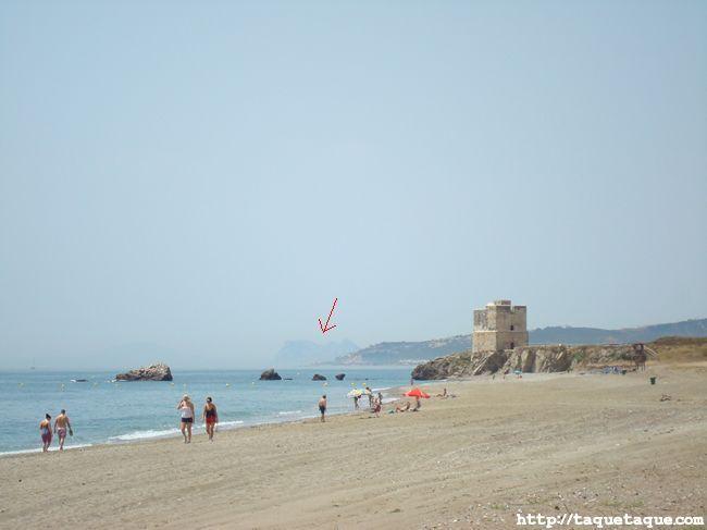 Playa con una torre árabe y el peñón de Gibraltar al fondo